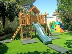 Play center, situated on artificial grass and with padded cushions for safety