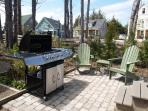 The backyard boasts a hot tub, an outdoor heated shower, a large propane grill and Adirondack chairs to relax in on the...