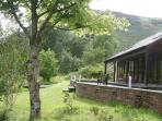 The Byre terrace onto wildlife garden, Ellas Crag behind.