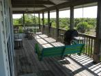 First floor deck with gas grill, table, and swing facing west toward Gulf