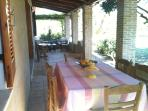 Large furnished veranda with dinner table for six and coffee table and sofa, too.