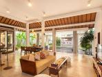 Open plan living and dining area with views to the pool and garden at Villa Malou in Seminyak.