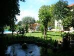 Vue du jardin, le petit lac, avec poissons rouges et, en arrière plan la piscine, barbecue et maison