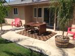Back patio has wooden table that can accommodate six plus hammock chair and lounge chairs also