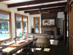 Sun drenched living/dining area w/bluestone fire place and custom handmade wooden beams
