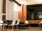 Living room at night, with soft lighting highlighting exposed brickwork and exposed beams