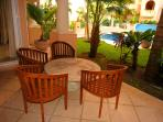 covered terrace with sitting area, charcoal grill and easy access to pool