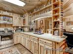This kitchen features beautiful shelving and is open to see right into the dining and living areas