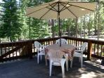 Back yard deck with table, umbrella, and BBQ grill all with forest views