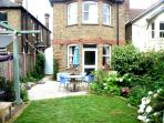 the back of the house with level garden access,table ,chairs gas BBQ and swing seat