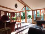 Bright sunny garden room with double doors leading onto patio and garden