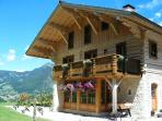 Chalet in the summer surrounded by wild flowers & panoramic mountain view