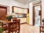 A modern kitchenette, equipped with a fridge and a freezer, toaster and Italian coffee maker.