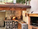 A large brick pizza oven, traditional barbeque and dining table.