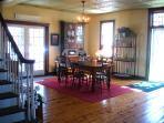 Open concept main floor with bright dining room with many doors and transom window