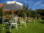 The private walled garden furnished with gold tables and chairs. Enjoy a cup of tea in the sunshine.