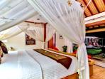 3 bedroom villa king size bed detail with view to the pool area right.