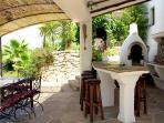 A shaded BBQ and outdoor kitchen/bar with fridge/freezer and dartboard