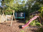 Play area with double swing, trampoline and slide.