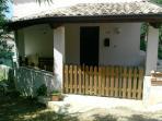 Entrata dell'immobile con veranda attrezzata da sedie tavolo e sdraio.