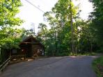 front of cabin with paved flat driveway on a peaceful road.