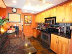 Beautiful kitchen with granite and stainless is well stocked for cooking