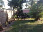 Backyard has wrought iron eating table with 4 chairs and a gas grill.