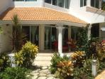 side view of our villa with little walk path going directly to spacious outdoor patio table chairs