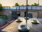 Enjoy outdoor dining by the pool next to granite counter top and bbq grill