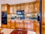 Another view of the spacious kitchen, stocked with amenities and appliances.
