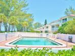 Gulf side Family Pool. Toy storage behind left fence. Tables chairs & loungers.