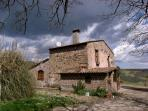 House in a sun-bathed valley, surrounded by undulating fields and olive groves.