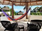 private palapa rooftop with loungers, hammocks, dining table and chairs