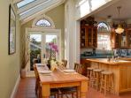 Sun-filled solarium and dining area with view to the garden.