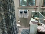 Guest Bath has a Shower Over Tub in soothing colors of the sea.