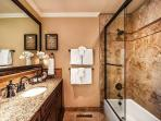 Luxurious bathroom has a shower over the tub.