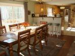 Main Dining Room is open to kitchen, has gas log fireplace, doors open to dining deck & water view