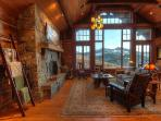 The great room with a beautiful rock fireplace and amazing mountain views