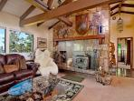 Spacious great room with vaulted beamed ceilings and fireplace.