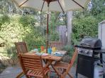 Private Patio with Magnificent Old Cypress Tree has Dining for 4 with a Gas BBQ.