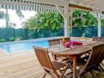 Le coin repas sur la terrasse couverte face à la piscine
