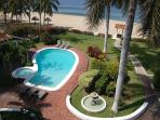 Manicured garden/pool area steps from the beach