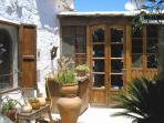 Entrance to porch of cortijo with stained glass window on left.