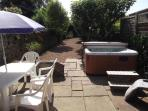 The back walled garden with Jacuzzi spa and three eating areas.