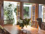 Dining room opening out through French doors to Jasmin arch