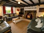 Large lounge with log burner, featuring original beams