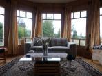 Sala de estar con tv cable, comedor y vista al fiordo y cordillera.