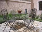 tavolino e sedie in ferro battuto sull'aia dell'incantevole giardino di erbe aromatiche
