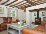 Lounge with exposed beams and woodburner