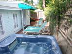 Sundance spa on private back deck with lounge chairs, hammock, dining table, BBQ